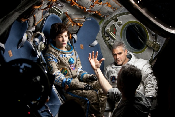 """(C) 2013 WARNER BROS. ENTERTAINMENT INC. Photo Credit: MURDO MACLEOD Caption: (L-r) SANDRA BULLOCK, GEORGE CLOONEY and director ALFONSO CUARÓN on the set of Warner Bros. Pictures' dramatic thriller """"GRAVITY,"""" a Warner Bros. Pictures release."""