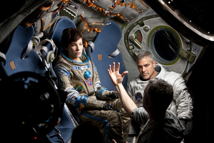 "(C) 2013 WARNER BROS. ENTERTAINMENT INC. Photo Credit: MURDO MACLEOD Caption: (L-r) SANDRA BULLOCK, GEORGE CLOONEY and director ALFONSO CUARÓN on the set of Warner Bros. Pictures' dramatic thriller ""GRAVITY,"" a Warner Bros. Pictures release."